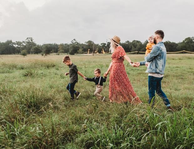 A family hold hands while walking through a field