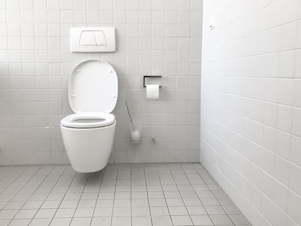 A toilet in a white public bathroom